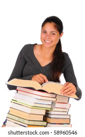 Smiling female teenage student behind a stacks of books. Vertical format isolated on white top book is open and girl is pointing at book.