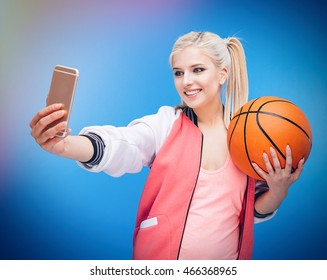 Smiling female teenager holding basketball ball and making selfie photo on smartphone over blue background
