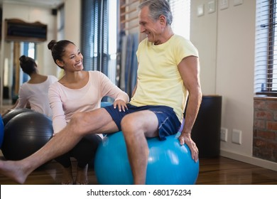 Smiling female therapist crouching by senior male patient sitting on exercise ball at hospital ward