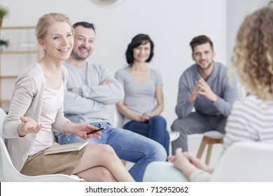 Smiling female therapist talking to people in support group, sitting with a notebook