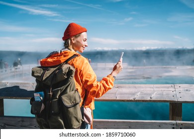 Smiling female tourist with big backpack standing near hot spring in Yellowstone National Park and doing video call on mobile phone - Shutterstock ID 1859710060