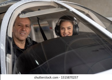 Smiling Female Trainee Pilot and Flight Instructor in an Aircraft Cockpit. Portrait of attractive young woman pilot with headset preparing to fly. She is sitting next to instructor and looking camera.