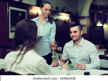 Smiling female waiter serving guests table in restaurant