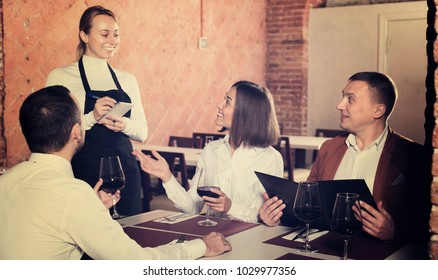 Smiling female waiter taking order from guests in country restaurant. Focus on man