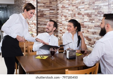 Smiling female waiter writing down order from visitors in restaurant