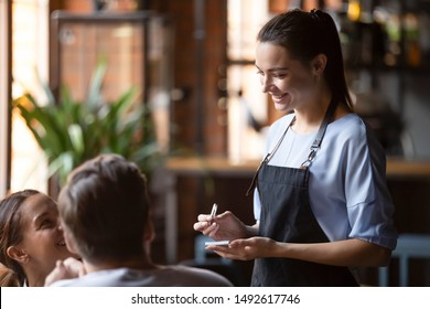 Smiling female waitress take order talk to clients cafe restaurant visitors couple, friendly professional woman server wear apron write dinner food menu choice, serving staff good customer service
