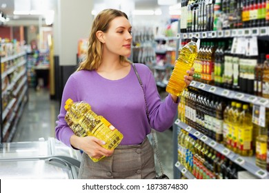 Smiling female want to buying bottle of oil.