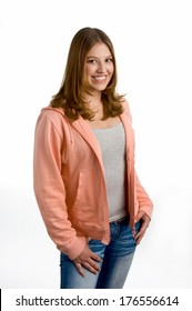 A smiling female wearing a pink zip up shirt and jeans.