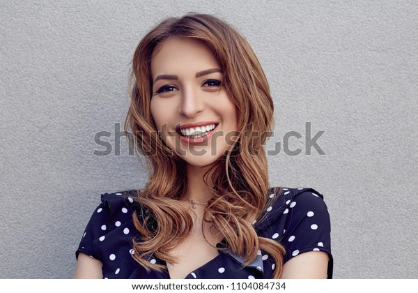 Smiling female with white teeth outdoor portrait. Happy Woman in dotted dress.