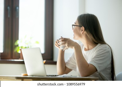 Smiling female worker looking in the window, taking break, having rest after work, enjoying coffee. Woman thinking about new opportunities, dreaming, being distracted from work.