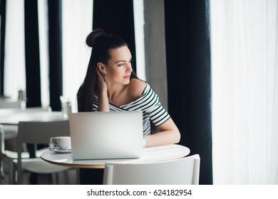 Smiling female writer is working with her new idea at lunch and looking through the window for searching for inspiration. Attractive adult woman sitting at the table with a cup of coffee and a laptop.