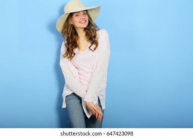 Smiling feminine womam looking camera, fashion, straw hat, outfit, clothes, figure,look on blue background