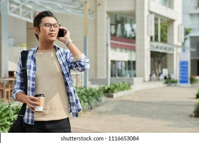 Smiling Filipino young man talking on phone and drinking coffee when walking in the street