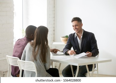 Smiling financial advisor consulting interracial couple about new house at meeting, friendly architect real estate agent discussing building plan with family clients, mortgage loan investment concept