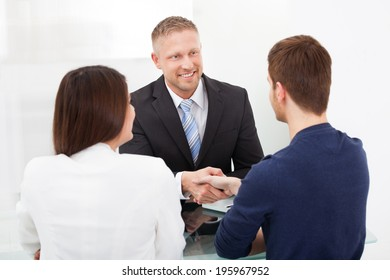 Smiling financial advisor shaking hand with young couple at office desk