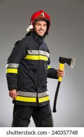 Smiling firefighter in red helmet holding an axe. Three quarter length studio shot on gray background.
