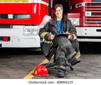 Smiling Firewoman Sitting On Chair Against Trucks