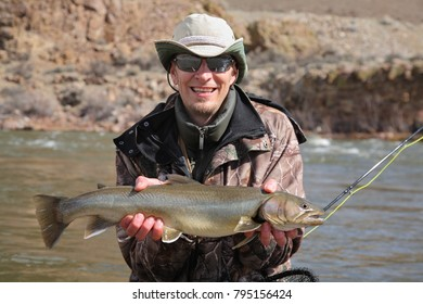 smiling fisherman with large bull trout
