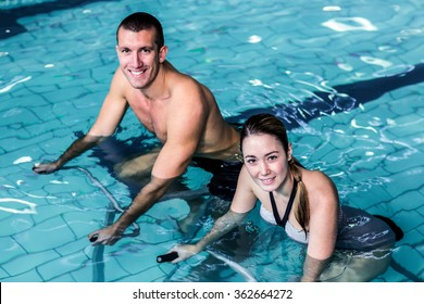 Smiling fit couple cycling in the pool