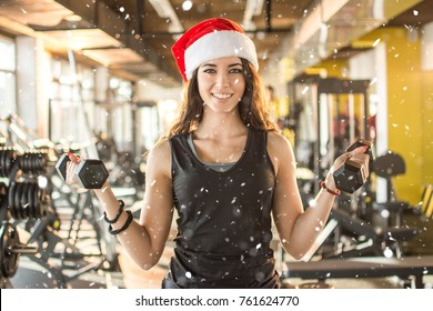 Smiling fit girl in Santa's hat with dumbbells in gym. Snow effect on image. New Year. Christmas, holidays, fitness, and gym concept.