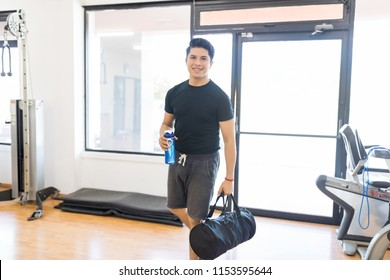 Smiling fit man with water bottle and gym bag entering in health club