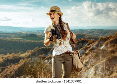 smiling fit solo tourist woman in hiking clothes with bag with binoculars looking into the distance on Tuscany summer hike.