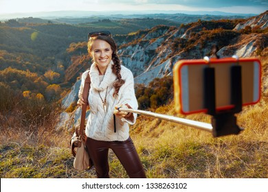 smiling fit solo traveller woman in hiking clothes with bag on summer Tuscany trail taking selfie using selfie stick.