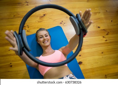 Smiling fit woman exercising with pilates ring on mat in fitness studio