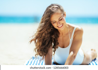 smiling fit woman in white swimwear laying on a striped towel on the seashore. Sunny summer midday. european woman with long brunette hair 30 something years old. quiet vacation heaven.