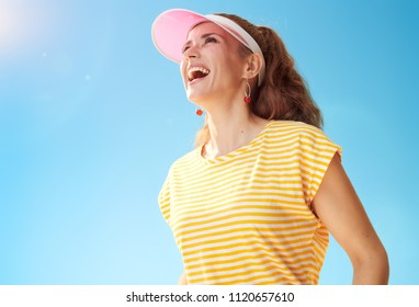 smiling fit woman in yellow shirt against blue sky looking into the distance