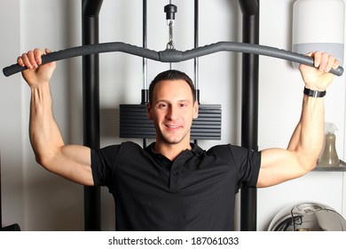 Smiling fitness guy working out in gym toning upper part of his body.