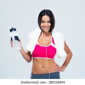 Smiling fitness woman holding bottle with water over gray background