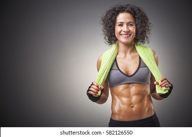 Smiling fitness woman posing with a green towel on grey background