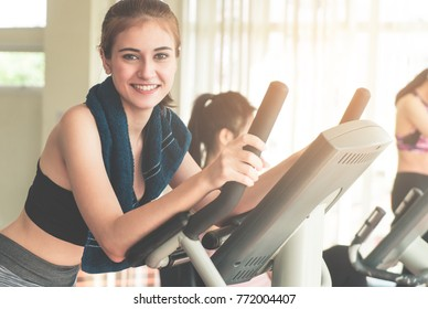Smiling Fitness woman is running on treadmill with friends on background
