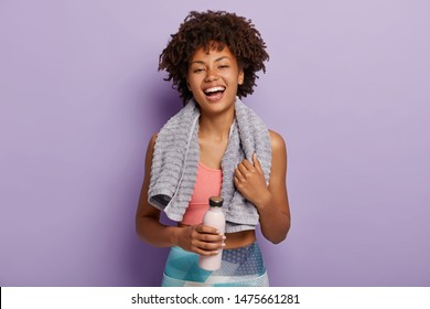 Smiling fitness woman in top and leggings takes break after training, holds bottle of water, wipes sweat with towel, being energetic runner or jogger, feels thirsty. People, wellness, vitality concept