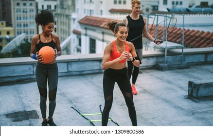 Smiling fitness women and a man doing fitness training on terrace. Man doing workout using skipping rope while his female colleagues training with agility ladder and basketball.