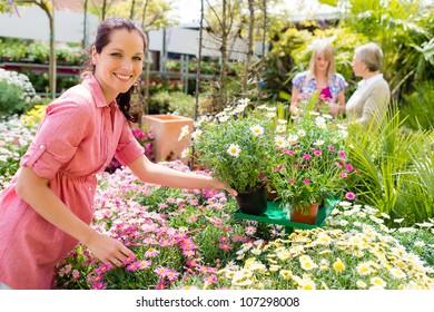 Smiling florist arranging flower pots in garden center greenhouse store