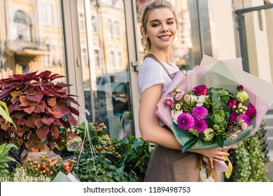 smiling florist holding beautiful bouquet of chrysanthemums near flower shop and looking at camera