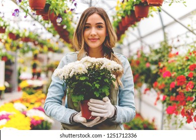 Smiling florist holding pot of flowers