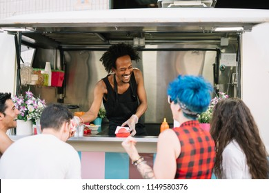 Smiling food vendor hands food to waiting customer