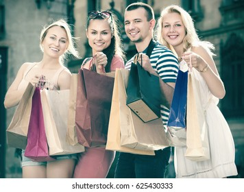 Smiling four people holding many shopping paper bags in town