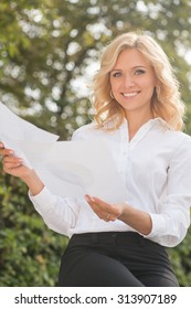 Smiling freelance lady sitting in the park and working. Beautiful woman in white shirt and black trousers looking at the camera.
