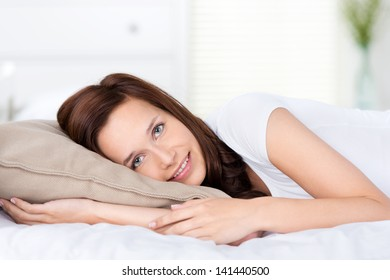 Smiling fresh woman lying on bed in a close up shot