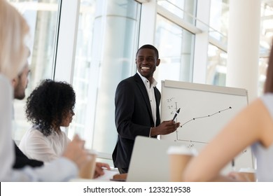 Smiling friendly african american businessman mentor giving presentation at diverse team office training, happy black coach satisfied with growth laughs speaks about good work result at group meeting