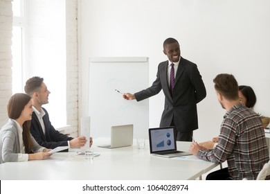 Smiling friendly african american coach in suit discussing business presentation with team people in meeting room, black ceo manager presenting new plan or project results to employees group