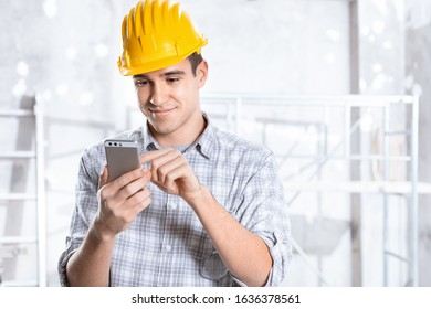 Smiling friendly architect, engineer or builder wearing a hardhat on a building site holding a mobile phone on which he is texting or dialling out