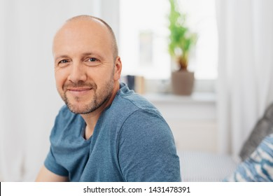 Smiling friendly attractive balding middle-aged man seated indoors at home looking at the camera with a happy warm smile