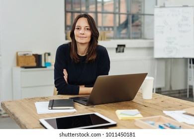 Smiling friendly attractive businesswoman seated at a wooden table in the office with a laptop leaning forwards to smile at the camera