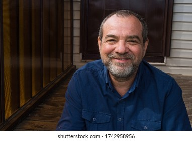Smiling friendly bearded adult man on the doorstep of his house close-up portrait