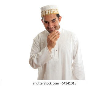 Smiling friendly ethnic man wearing a traditional embroidered robe with ruby buttons and a white and gold embroidered topi hat.  White background.